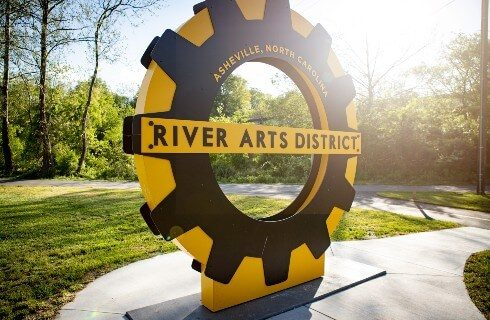Large yellow and black circular sign for a local arts district