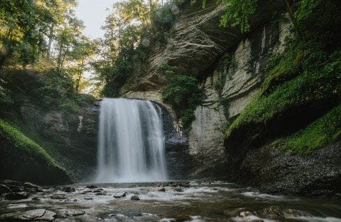 A waterfall cascading into a rocky stream surrounded by trees and rock formations