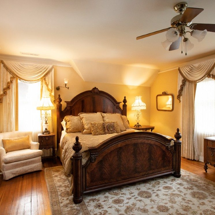 Elegant bedroom in golds and ivory with king bed, bedside tables with lamps and white sitting chair