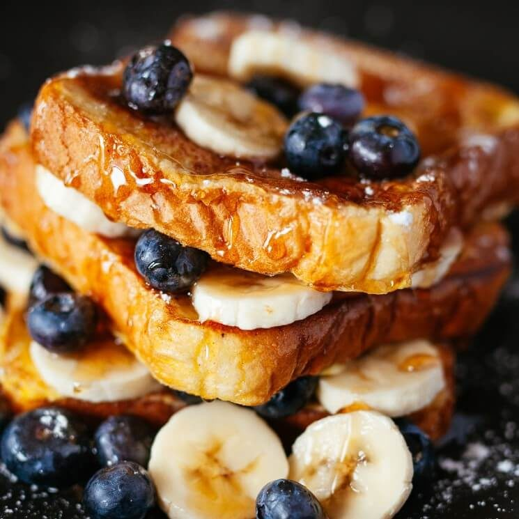 A stack of golden brown pieces of French toast with blueberries, bananas and drizzled syrup