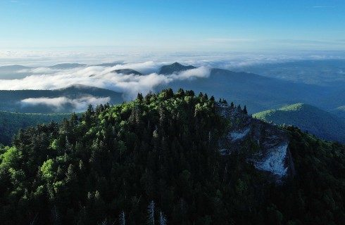 View at the top of a forest covered mountain range with whisps of clouds in the sky