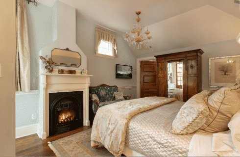 Elegant bedroom in white and ivory with queen bed, fireplace and tall mirrored armoire