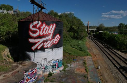 Railroad tracks in the middle of trees with an old silo with colorfu graffiti