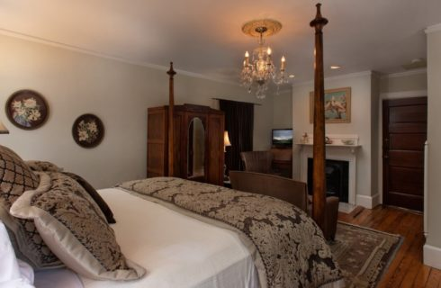 Four post bed in room with chandelier, tall armoire with mirror and fireplace