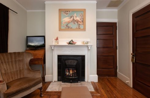 Bedroom with cozy fireplace, wingback sitting chair and hardwood floors