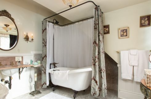 Beautiful antique bathroom with white clawfoot tub, round antique mirror and folded white towels on the wall