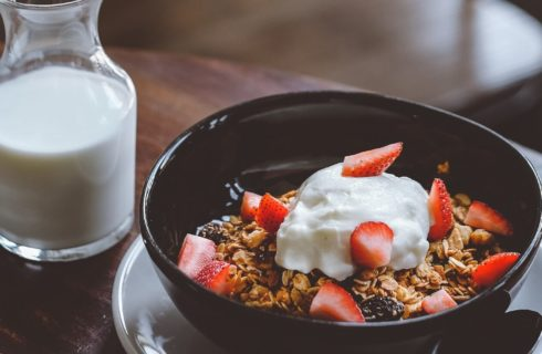 Small black bowl holding granola, berries and yogurt with small carafe of white milk