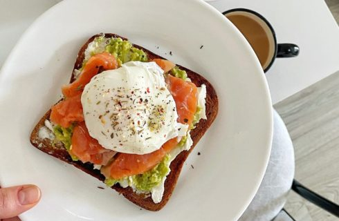 Golden brown piece of toast with avocado, salmon and a poached egg on a white plate