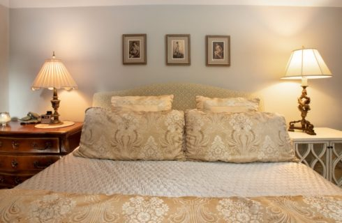 King size bed with upholstered headboard, luxurious linens and bedside table with white lamps