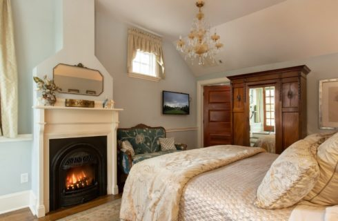 Cozy bedroom with white fireplace, king size bed, green sitting chair and tall mirrored armoire