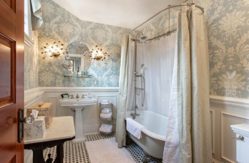 Beautiful antique bathroom with white clawfoot tub and round mirror over a pedestal sink