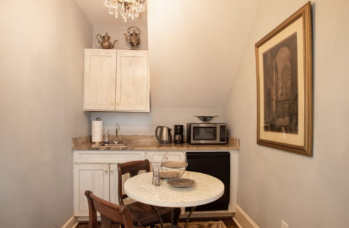Small kitchenette with white cabinets, granite countertop and table with two brown chairs