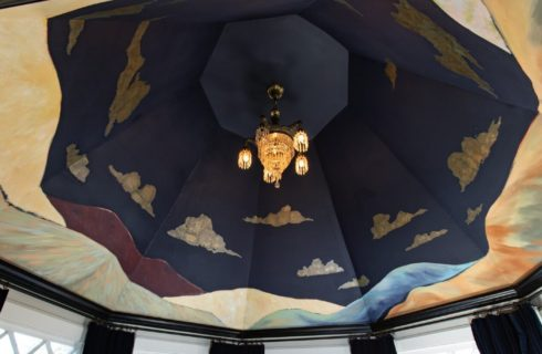 A Gaugin-inspired nighttime sky mural on a ceiling above a bed