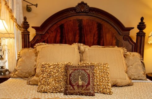 A luxurious king-size bed in shades of ivory and gold with large wooden headboard