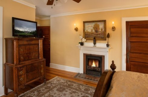 Corner of a bedroom with a white fireplace, wooden chest with a TV and oriental rug on the floor