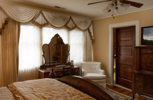 Luxurious bedroom in shades of gold and ivory with dresser and mirror, sitting chair and large chest with TV
