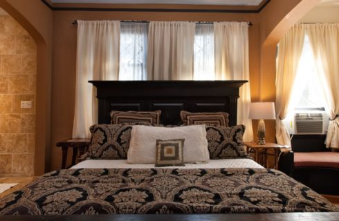 King bed with black headboard in bedroom with corner sitting nook and fireplace