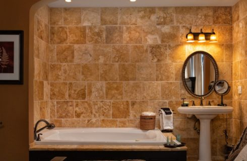 Travertine marble, 2-person jacuzzi tub next to a pedestal sink under an oval mirror