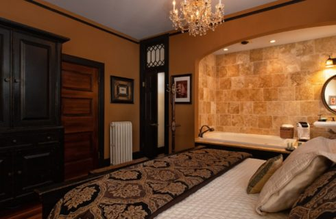 Travertine marble, 2-person jacuzzi tub and pedestal sink with mirror in guest room with a king bed and crystal chandelier