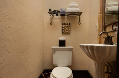 Single white toilet in bathroom with shelf holding toiletries and towels and pedestal sink under large mirror