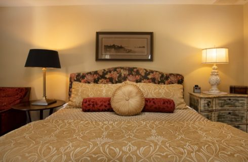 Plush king bed with flowered upholstered headboard, side tables with lamps and red sitting chair