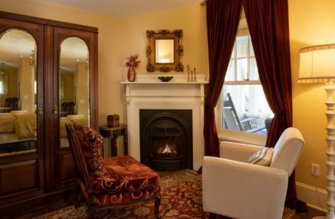 Two sitting chairs in front of a gas fireplace with a floor lamp and large mirrored armoire