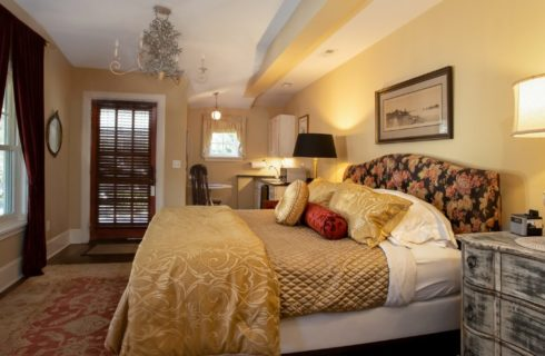 King bed with floral headboard in bedroom with mini kitchenette and large windows