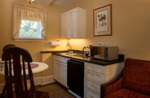 Mini kitchenette with white cabinets, granite countertop and table with two chairs
