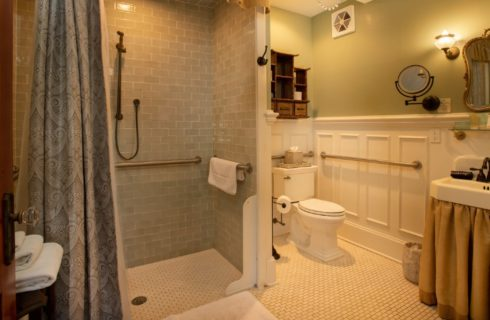 Spacious bathroom with roll in shower and white sink under large antique brass mirror