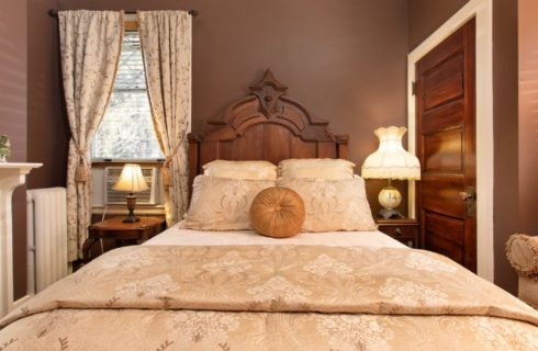 Queen bed with tall decorative headboard in cozy bedroom with gas fireplace and window seat