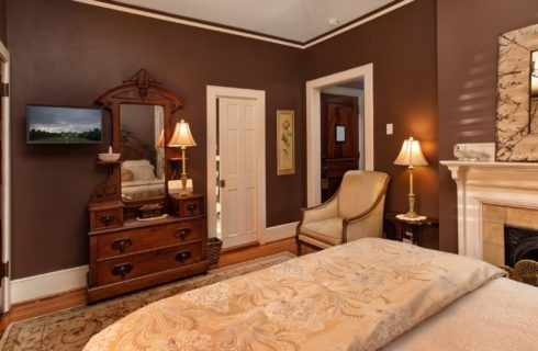 Romantic bedroom with chocolate brown walls, gas fireplace, dresser with mirror and queen bed