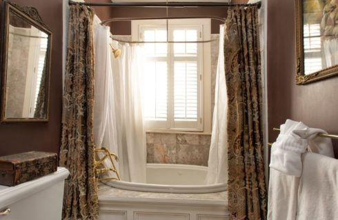 Jacuzzi bathtub and shower in a nook under a bright window with white towels hanging on gold rods