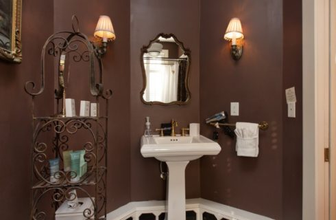 Corner of a bathroom with white pedestal sink under an antique mirror and decorative metal shelving holding toiletries