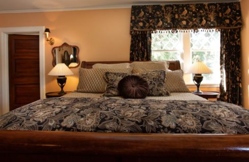 A magnificent king-size sleigh bed in a room with peach walls and large window flanked with curtains