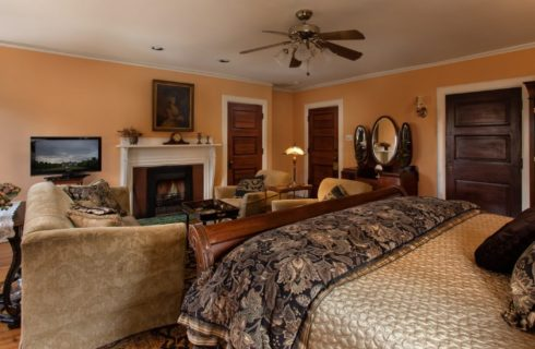 Spacious guest room with king-size sleigh bed and sitting area with couch and two chairs in front of gas fireplace