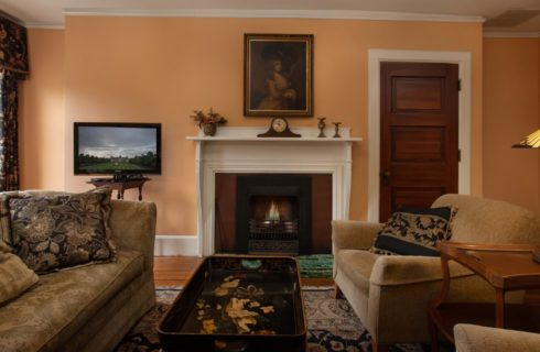 Sitting area with a couch, two chairs and coffee table in front of a white gas fireplace