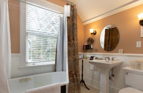 Bright bathroom with clawfoot tub and shower and pedestal sink under a large round mirror