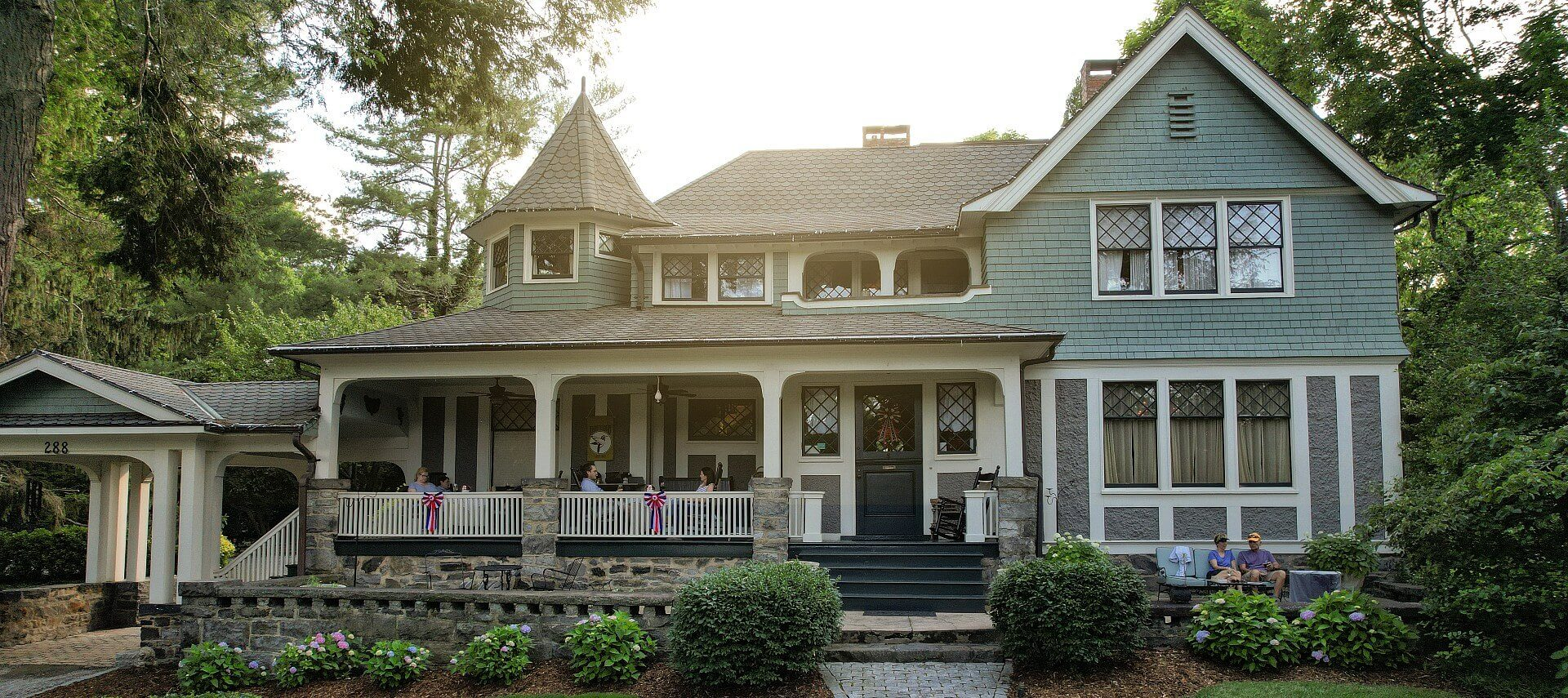 Front facade of a large home with porch, columns, side portico and lush landscaping