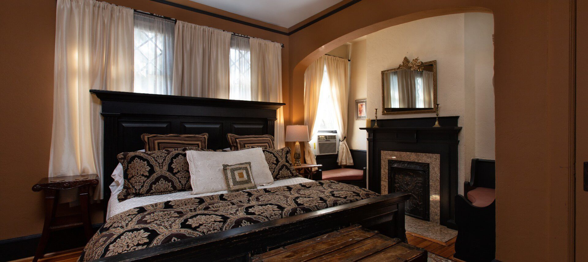 Elegant bedroom with black king size bed and fireplace with two sitting chairs through an arched doorway