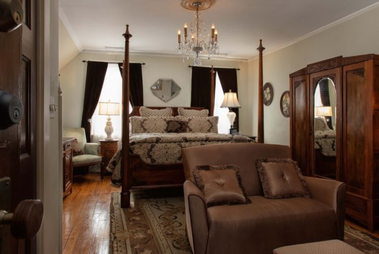 Spacious bedroom with four poster bed, armoire with mirror, sitting area and large windows