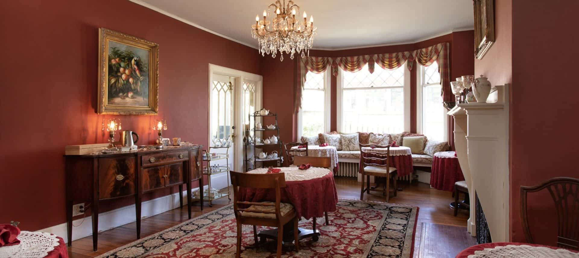 Luxurious and elegant dining room with tables set for two, antique buffet and window seat with pillows