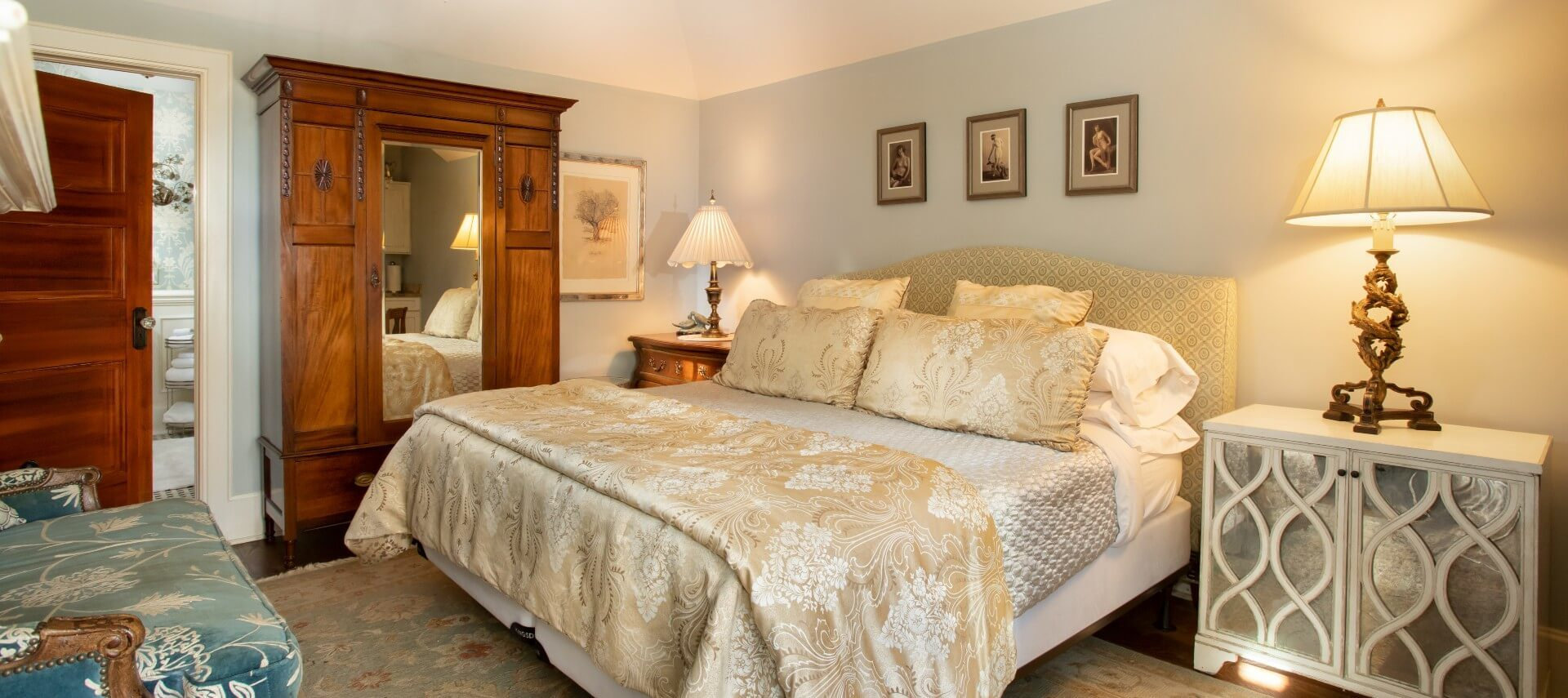 Bedroom with king size bed, tall armoire with mirror, sitting chair and bedside tables with lamps