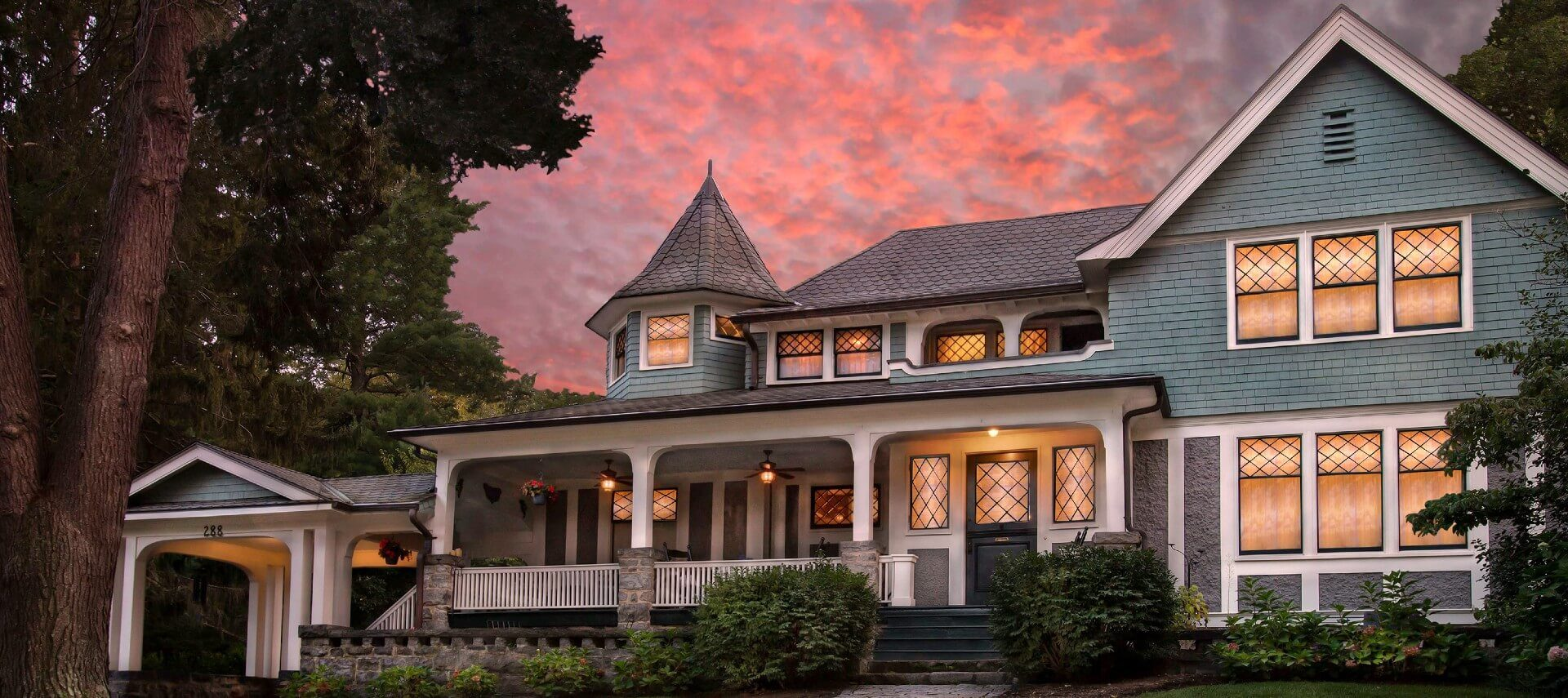 Front facade of a home with large front porch, white columns and soft glowing light coming from the many windows