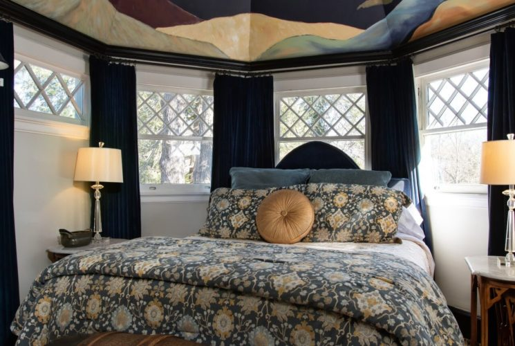 Bedroom with queen bed set within a bay window and a Gaugin-inspired nighttime sky mural overhead