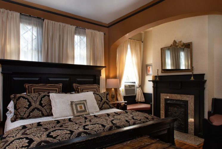 Bedroom with impressive black king size bed and fireplace and sitting chairs through an arched doorway