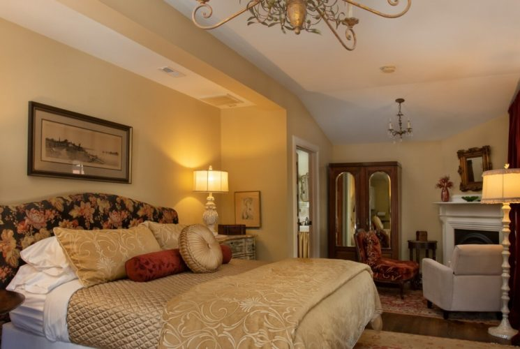 Bedroom with plush king-size bed, gas fireplace and sitting chairs