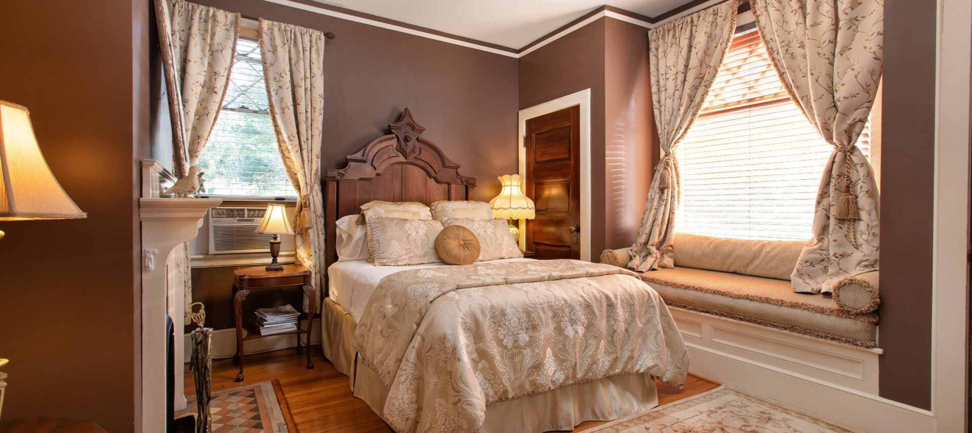 Romantic bedroom with queen bed, gas fireplace and window seat with plush cushions