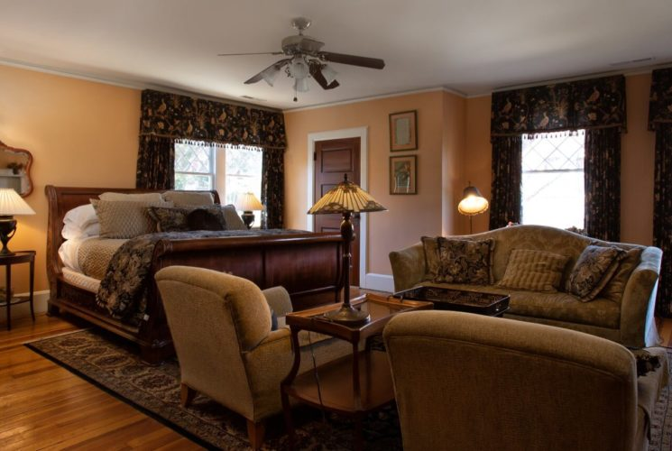 Spacious guest room with magnificent king-size sleigh bed and sitting area with a couch and two chairs