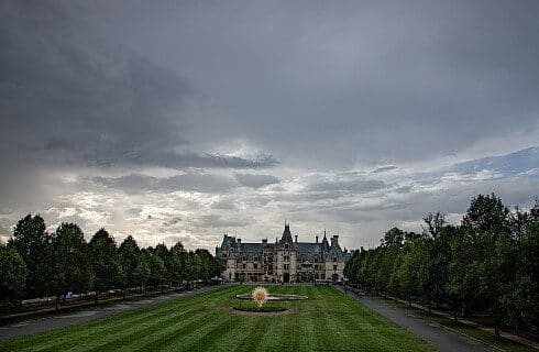 A massive estate at flanked by rows of trees with expansive green lawn and cloudy skies overhead