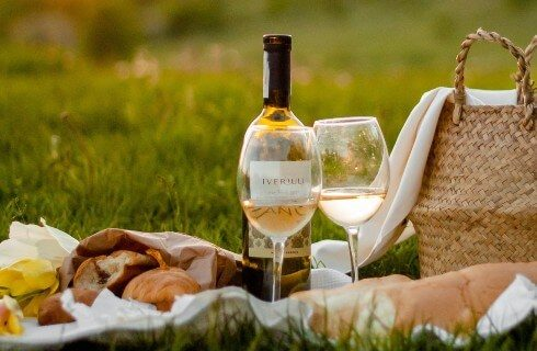 Picnic basket with blanket set out with bottle of white, two glasses and baguettes of bread